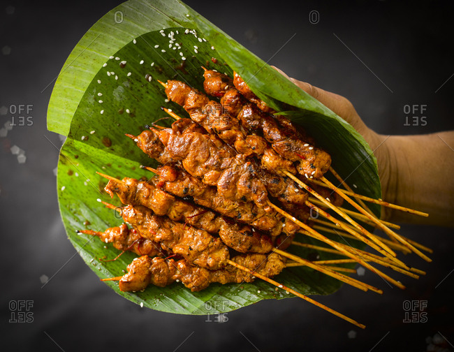 Chicken satay skewers and banana leaf