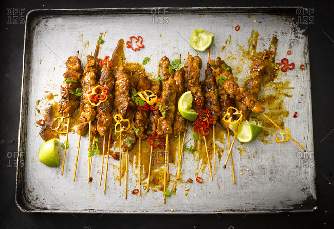 Chicken satay skewers with chili peanut sauce on baking tray