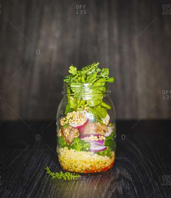 Preserving jar of buckwheat salad with vegetables - coconut chips and diced Striploin Steak