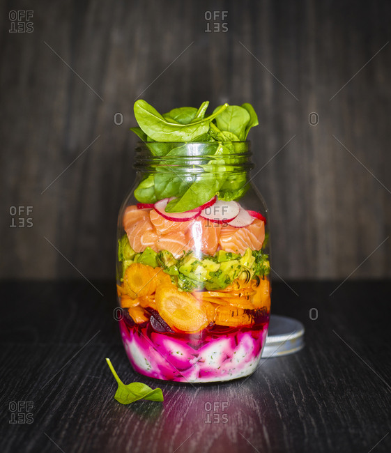 Preserving jar of salad with vegetables and salmon