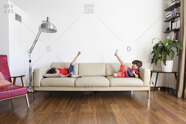 Twin brothers lying on the couch having fun