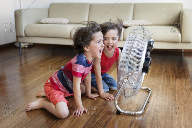 Twin brothers kneeling in front of fan having fun