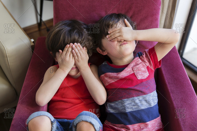 Twin brothers sitting together on arm chair covering eyes with hands