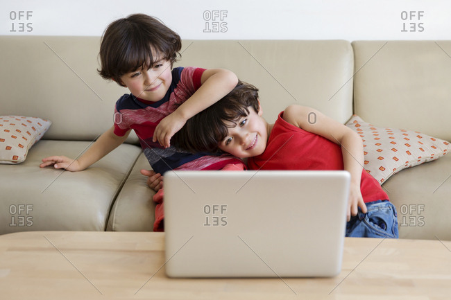 Twin brothers sitting on the couch looking at laptop