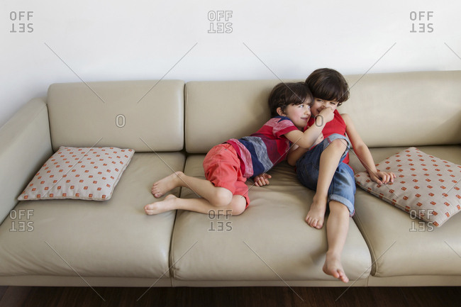 Twin brothers having fun together on the couch