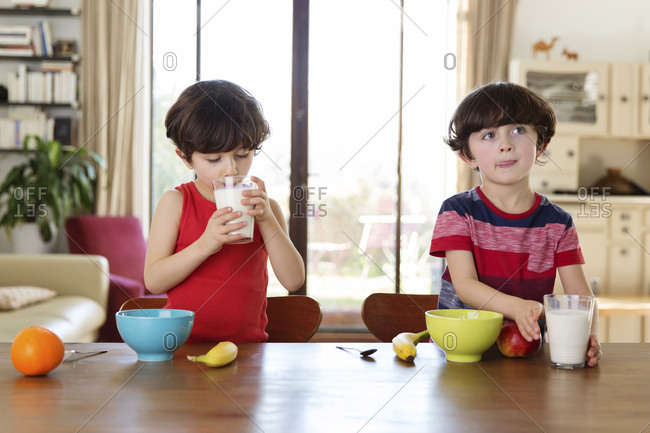 Twin brothers at the breakfast table drinking milk