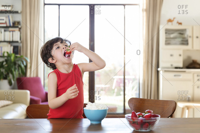 Little boy eating strawberry with whipped cream at home