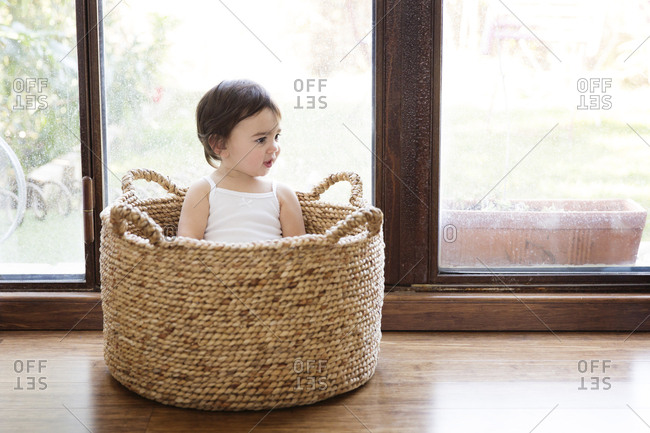 Toddler girl sitting in a basket in front of terrace door