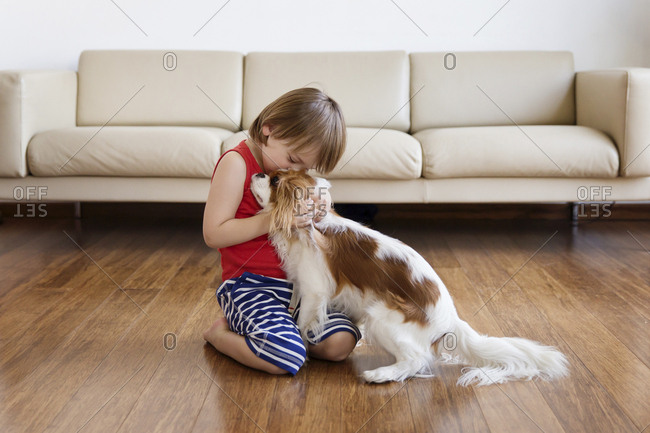 Little boy cuddling his dog in the living room