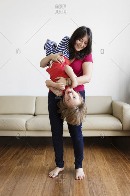 Smiling mother holding her little son upside down in the living room