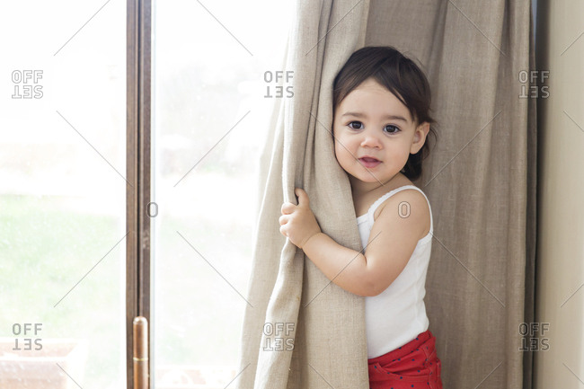Portrait of a toddler girl playing peek-a-boo behind the curtain