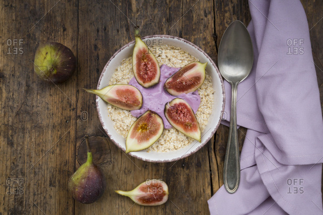 Bowl of overnight oats with blueberry yoghurt and figs on wood