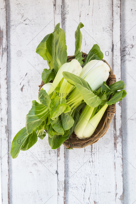 Wickerbasket of mini Chinese cabbage on wood