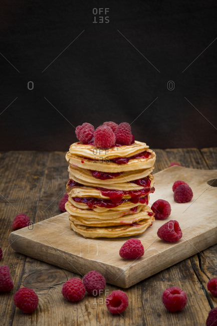 Stack of pancakes with raspberries and raspberry jam on wooden board
