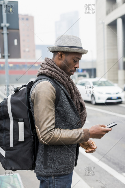 Stylish man with backpack standing beside road looking at cell phone