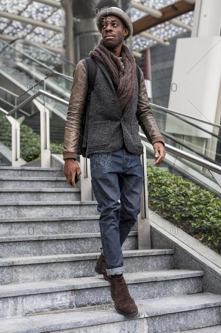 Stylish man wearing autumn fashion walking down stairs