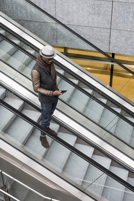 Young man standing on escalator looking at cell phone