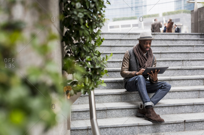 Man sitting on staircase using tablet