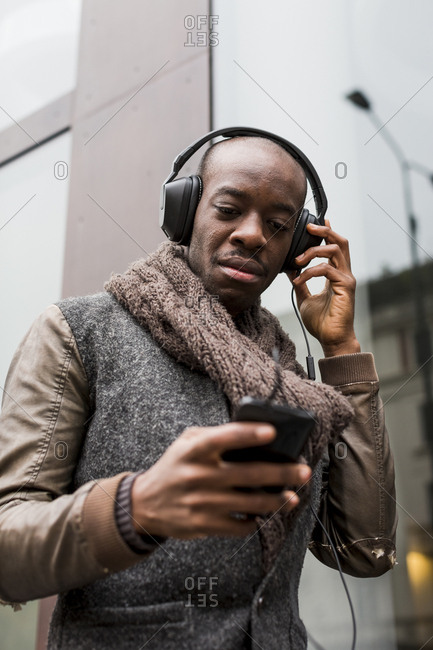 Bald man listening music with headphones looking at cell phone