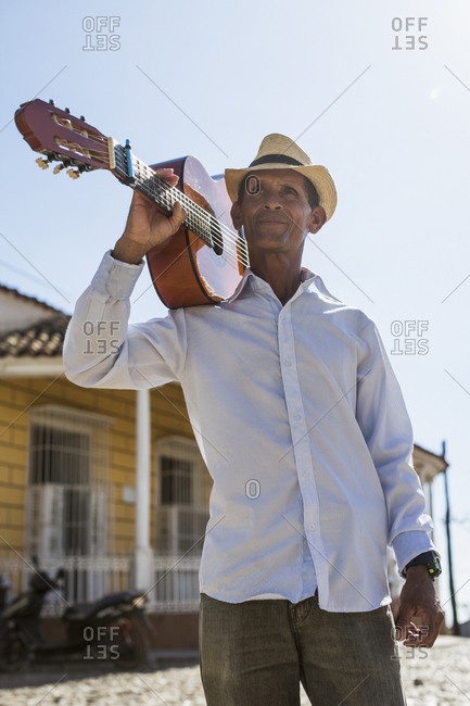 Cuba - portrait of man with guitar on his shoulder