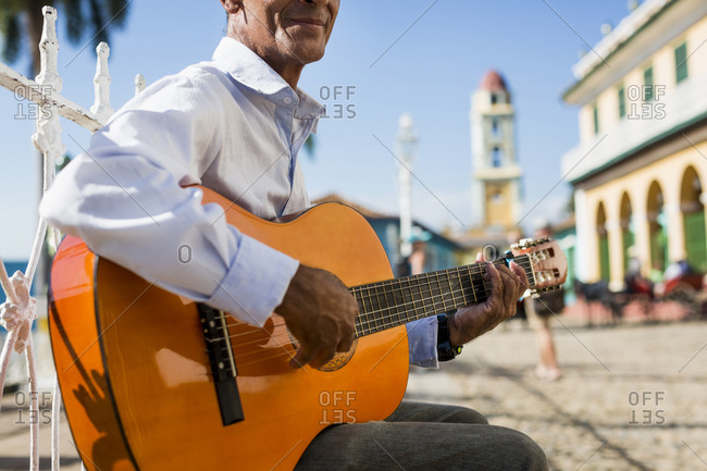 Cuba - Trinidad - man playing guitar on the street - partial view