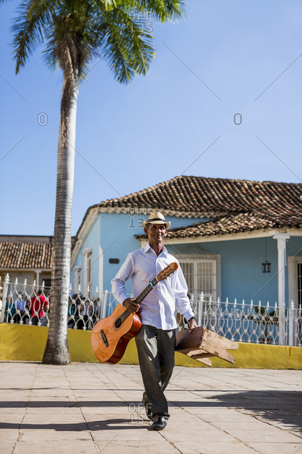 Cuba - walking man with guitar and stool on the street