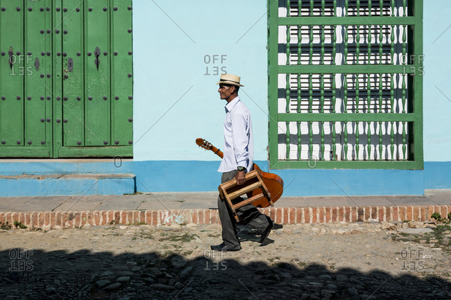 Cuba - Trinidad - walking man with guitar and stool on the street