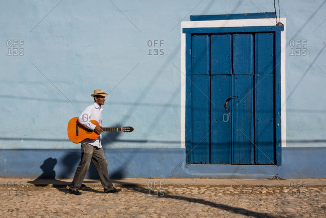 Cuba - man with guitar walking on the street
