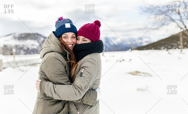 Two young women hugging in the snow