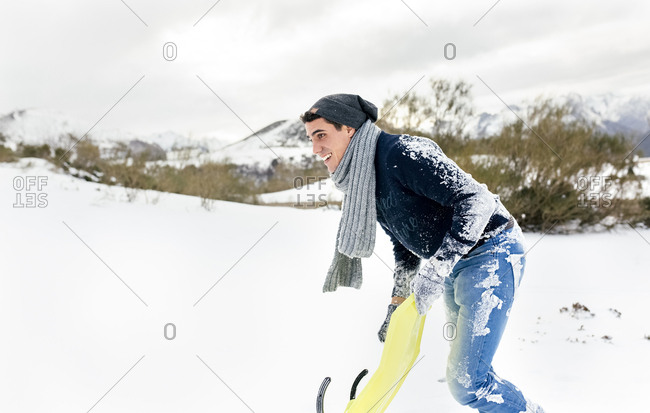 Young man having fun with a sled in the snow