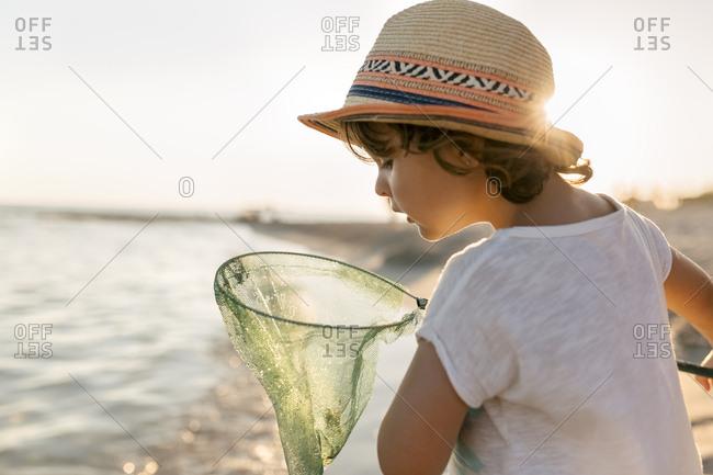 Spain - Menorca - little girl with a dip net on the beach
