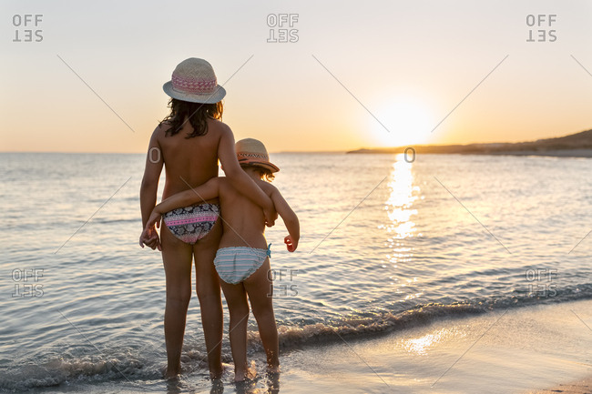 Spain - Menorca - two girls watching the sunset on the beach