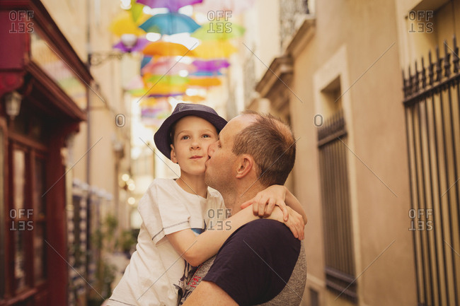 France - Languedoc - Beziers - father kissing son with colorful umbrellas in background