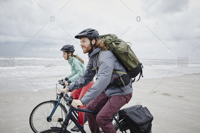 Germany - Schleswig-Holstein - St Peter-Ording - couple riding bicycle on the beach