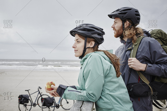 Germany - Schleswig-Holstein - St Peter-Ording - couple on a bicycle trip having a break on jetty at the beach