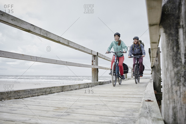 Germany - Schleswig-Holstein - St Peter-Ording - couple riding bicycle on jetty at the beach