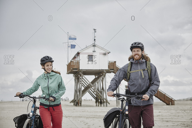 Germany - Schleswig-Holstein - St Peter-Ording - couple pushing bicycles on the beach