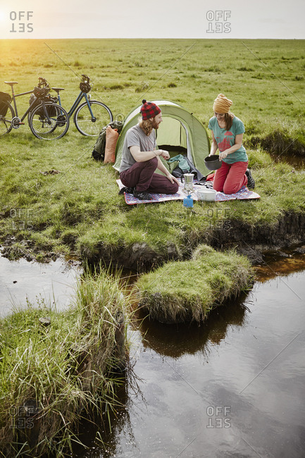 Germany - Schleswig-Holstein - Eiderstedt - couple with bicycles camping in marsh landscape