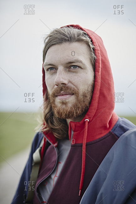 Portrait of confident man wearing hoodie outdoors