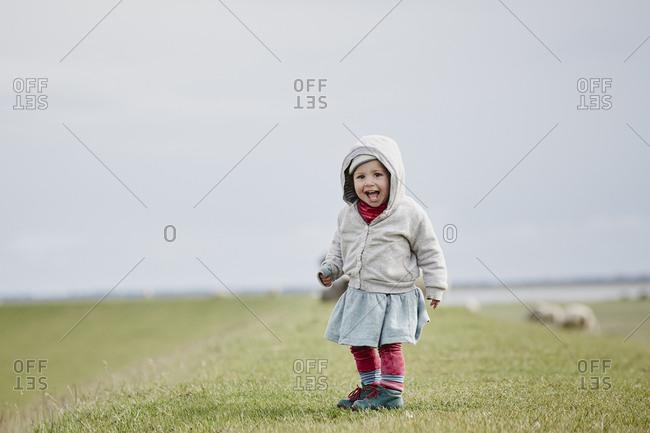 Germany - Schleswig-Holstein - Eiderstedt - happy little girl standing on dyke