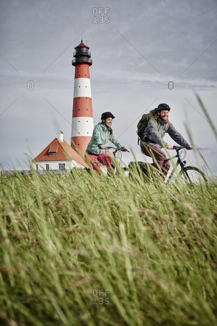 Germany - Schleswig-Holstein - Eiderstedt - couple riding bicycle near Westerheversand Lighthouse
