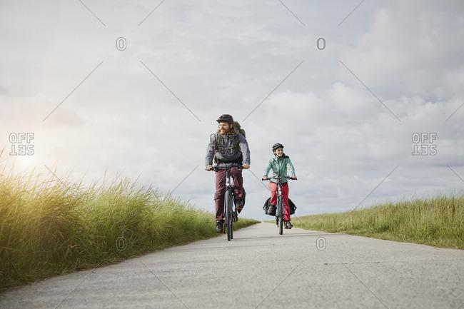 Germany - Schleswig-Holstein - Eiderstedt - couple riding bicycle on path through salt marsh
