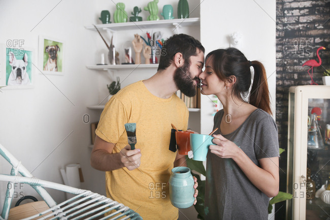 Young couple kissing between paintbrushes and tea mugs