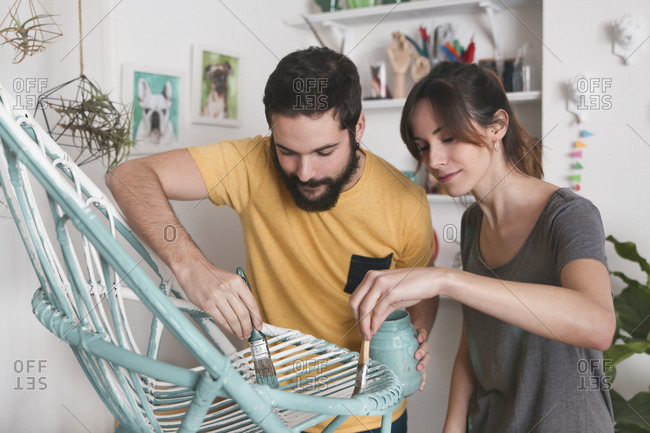 Young couple painting wicker armchair at home