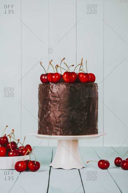 Cake with chocolate icing and cherries on top on cake stand