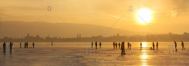 Germany - January 27, 2017: Lake Constance Hegne - silhouettes of ice skaters and walkers in front of Reichenau at sunset