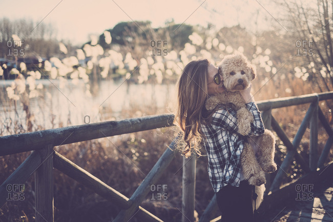 Woman standing on bridge holding her dog