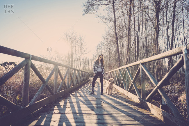 Woman standing on bridge with her dog
