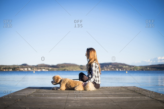 Woman sitting on jetty with her dog