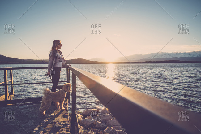 Woman at lake watching sunset with her dog